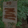 Rick ducks behind No Sanctuary sign